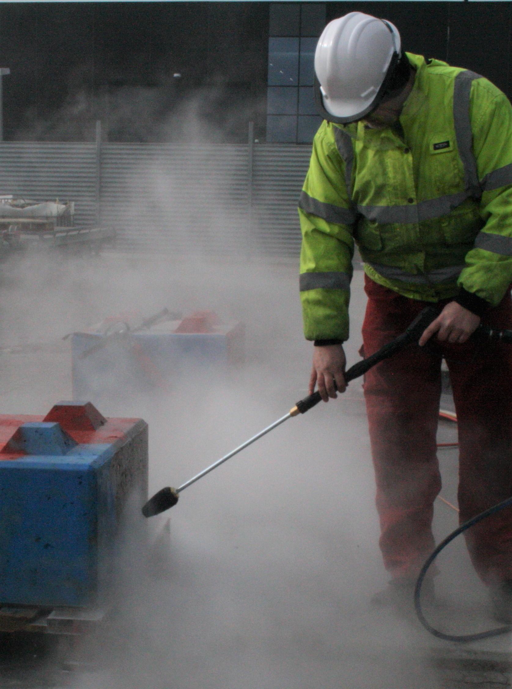 Heine foretager grafittiafrensning med en højtryksrenser